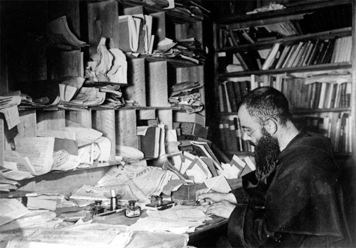 St. Maximilian Kolbe, patron of journalists, writing at his desk.