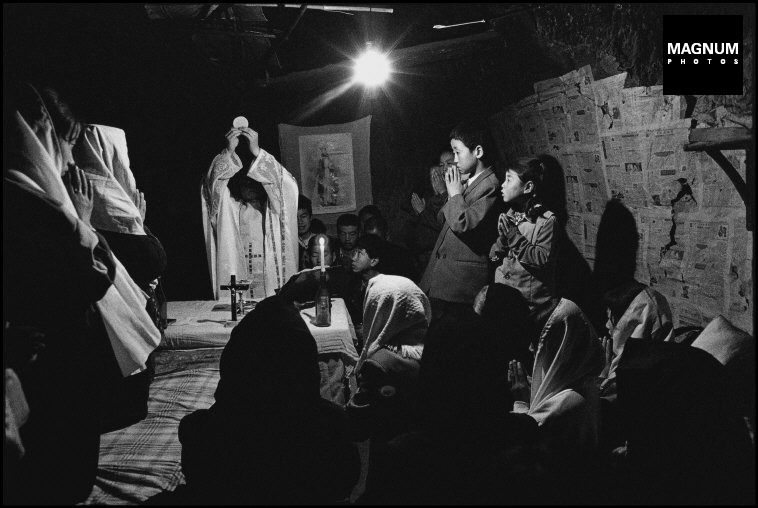 CHINA. Shaanxi Province. 1995. Mass is given in a member's residence in a village with no local church. Mass in a family house is officially prohibited by the Government, but the 'unofficial' churches take the risk.