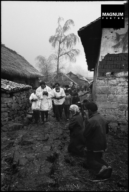 CHINA. Yunnan Province. 1996. A priest consecrated bread signifying the body of Jesus Christ. Behind him are members of the church.