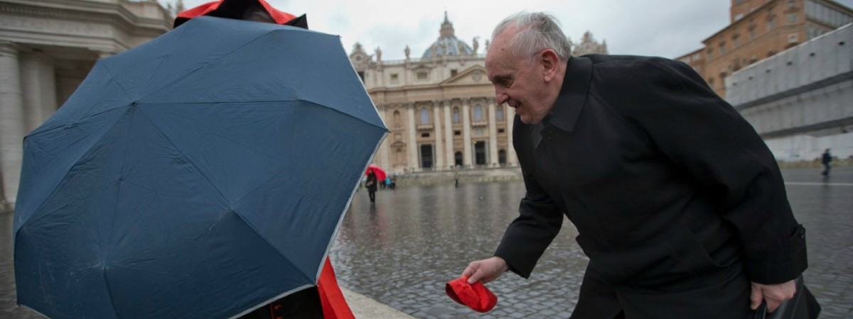 Pope Francis (when he was Bergoglio) helping another cardinal catch his hat in the wind