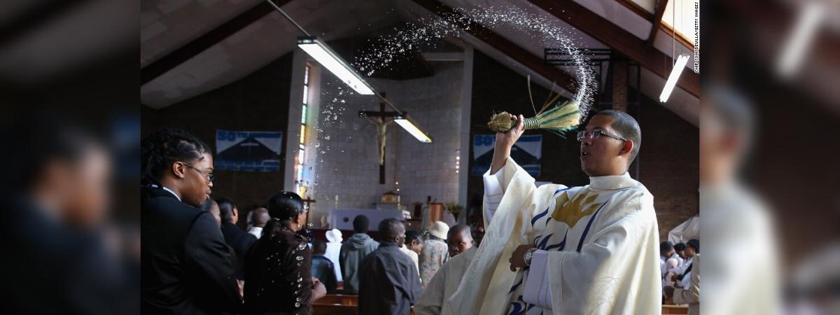 sacerdote usando agua bendita